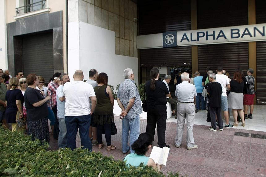 People queue to withdraw money from an ATM outside a branch of Greece's Alpha Bank in Athens, Greece on Sunday.