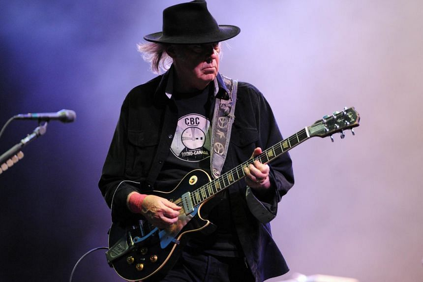 Canadian guitarist Neil Young performing on stage with his band The Crazy Horse at the Vieilles Charrues festival in Carhaix-Plouguer, western France in 2013.  Young, nearly 70 years old, goes to war against Monsanto and GMOs in a new album -availabl