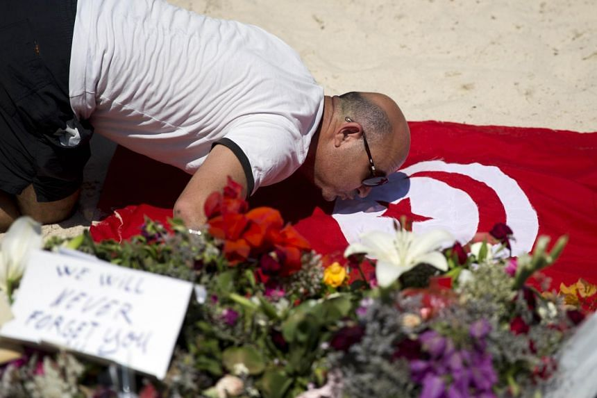 A man kisses a Tunisian flag at the site of a shooting attack on the beach in front of the Riu Imperial Marhaba Hotel in Port el Kantaoui, on the outskirts of Sousse south of the capital Tunis, on Sunday. ISIS claimed responsibility for the massacre