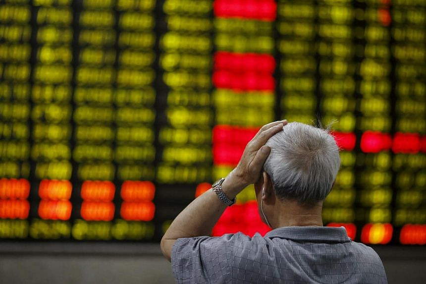 An investor looks at an electronic board showing stock information at a brokerage house in Shanghai on June 16, 2015.
