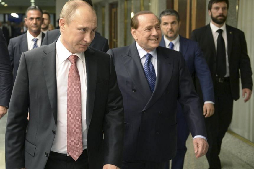 Russian President Vladimir Putin (left) and Italian former Prime Minister Silvio Berlusconi (second, left) walk during their meeting in Italy, June 10, 2015.
