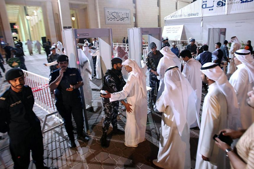 Kuwaiti mourners queue to be searched by security members outside the Sunni Grand Mosque on June 27, 2015 as they arrive to give their condolences to the families of the victims of a suicide bombing which took place at the Shiite al-Imam al-Sadeq mos