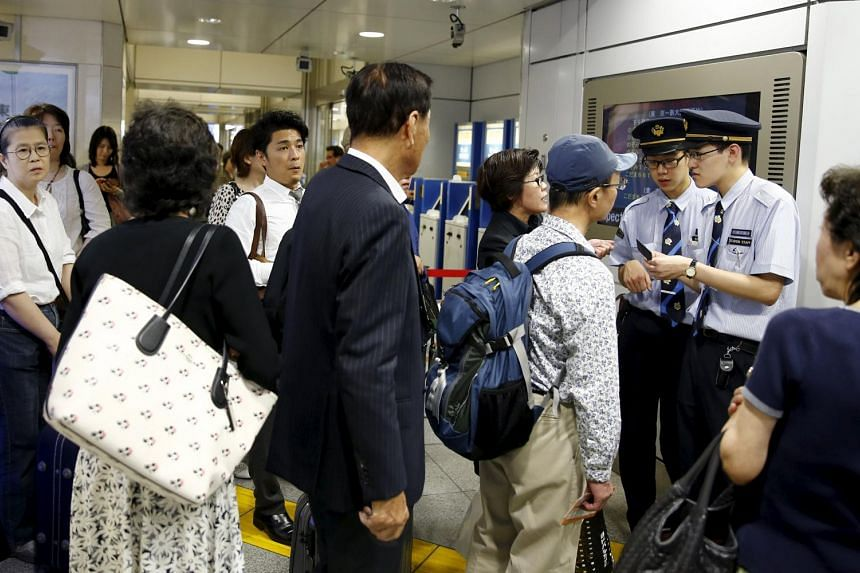 Passengers talking to station staff at the gates to the bullet train tracks in Tokyo.