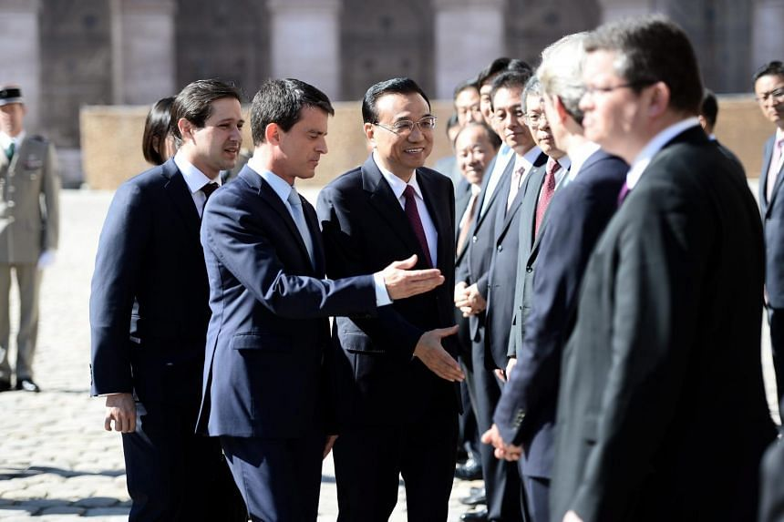 French Prime Minister Manuel Valls (second-Left) and his Chinese counterpart Li Keqiang (centre) attend a welcoming ceremony at the Hotel National des Invalides, in Paris, France on June 30, 2015.