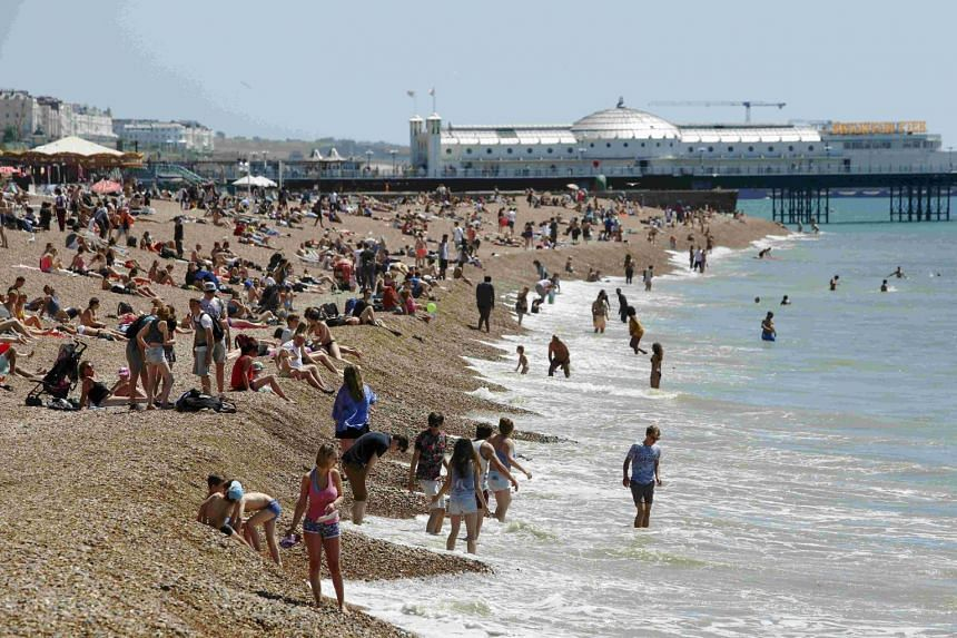 Sunbathers and swimmers enjoy a hot Summer day at Brighton beach in Britain on June 30, 2015.