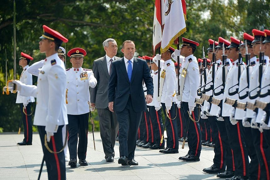 Mr Tony Abbott inspecting the guard of honour with PM Lee Hsien Loong at the Istana yesterday, during the Australian Prime Minister's two-day official visit to Singapore.