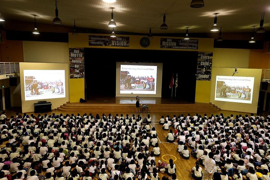 Tanjong Katong Primary School principal Caroline Wu addressing the pupils yesterday during the morning assembly, where she called on them to be strong and move on. At the entrance to the school, sunflowers and balloons (below) greeted the pupils as t