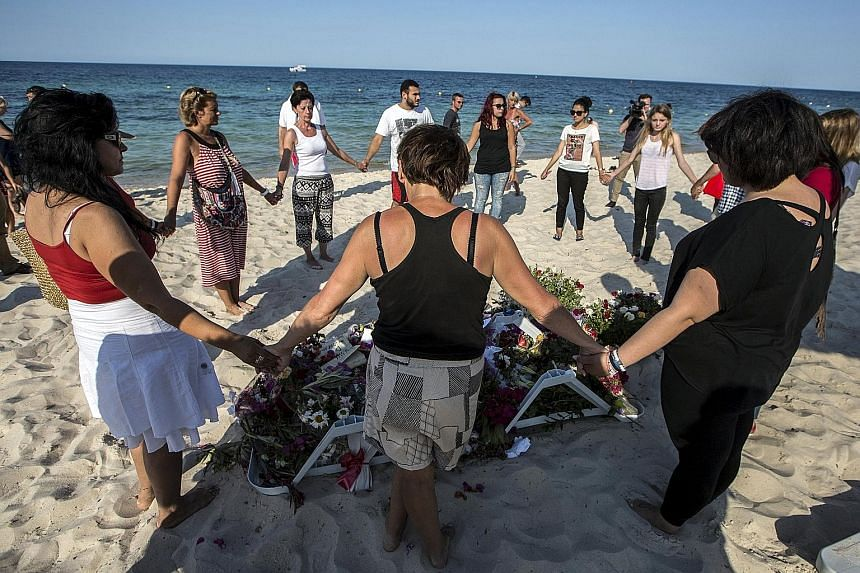 People praying around bouquets of flowers laid in memory of the victims at the Imperial Marhaba resort. Last Friday, a Tunisian student disguised as a tourist opened fire on holidaymakers killing 39 and wounding 38. The Tunisian government said armed