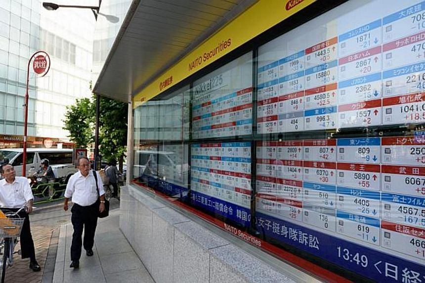 Pedestrians look at an electronic stock board outside a securities firm in Tokyo, Japan, on June 24, 2015.