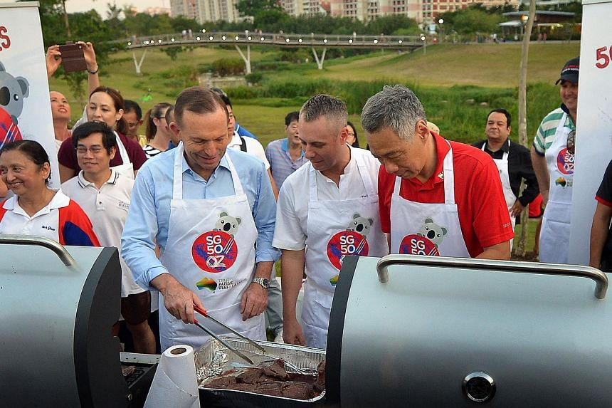 Prime Minister Lee Hsien Loong and his Australian counterpart Tony Abbott (left) grilling some steaks at Bishan Park with Australian celebrity chef Dallas Cuddy (centre) on June 28, 2015.