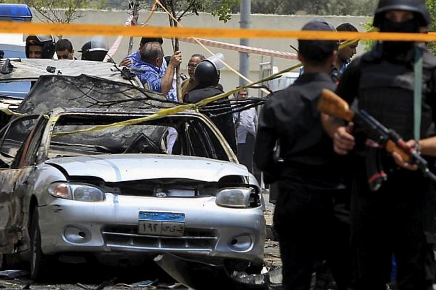 Policemen secure the site of a car bomb attack on the convoy of Egyptian public prosecutor Hisham Barakat near his house at Heliopolis district in Cairo, Egypt, June 29.