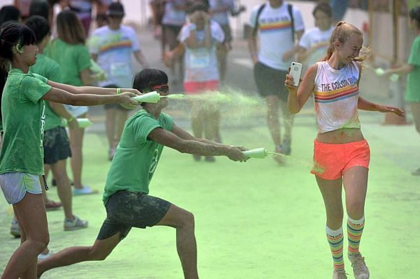 A participant getting splashed with green-coloured powder during the Colour Run on Aug 30, 2014.
