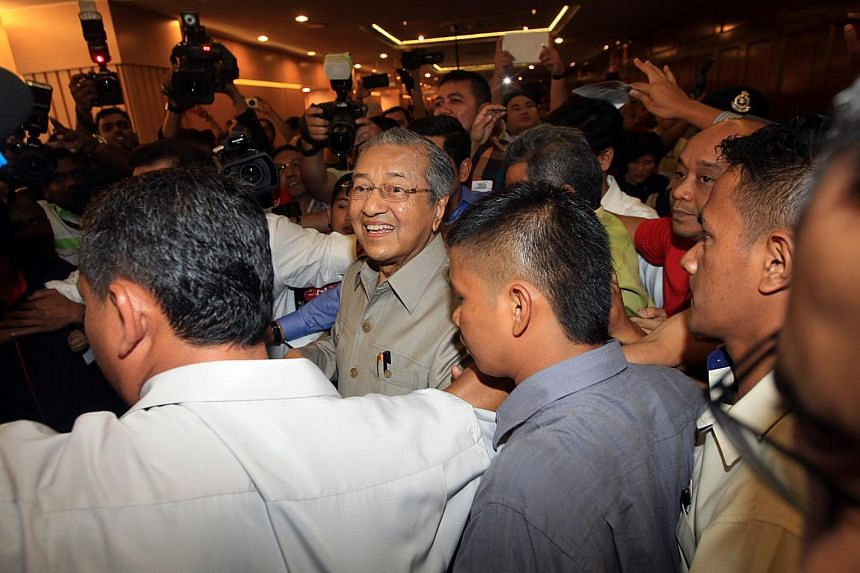 Dr Mahathir Mohamad being escorted out soon after a police officer stepping onstage to ask Dr Mahathir to stop speaking at the Nothing2Hide forum on June 5, 2015.