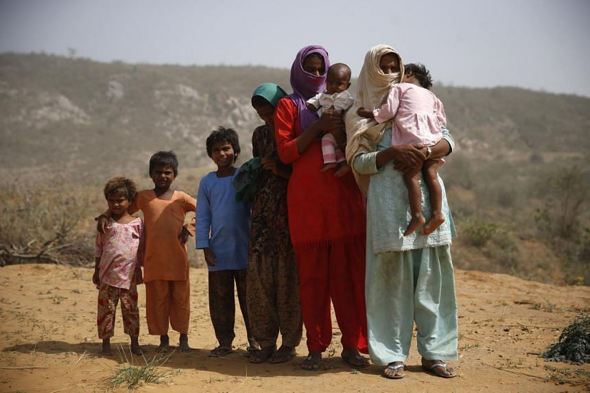 A victim of bride-trafficking (right, with white headdress) with her six daughters at home in Haryana, India. The eldest daughter (second from right, with purple headdress) has been married off by the mother to prevent her from suffering the same fat