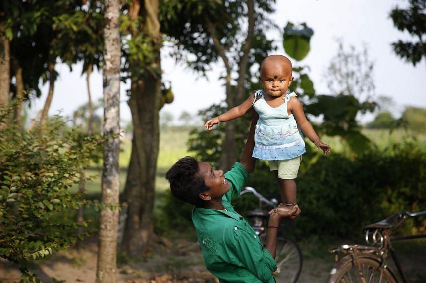 A baby girl is lifted by her older relative in a village in West Bengal, India.