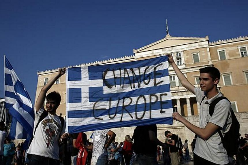 """Protesters holding a Greek flag with the words """"change Europe"""" during an anti-austerity rally in Syntagma Square."""