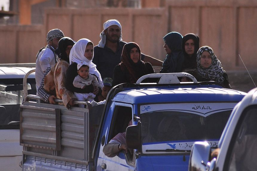 Displaced Syrians fleeing from Hasakeh due to attacks by the Islamic State in Iraq and Syria (ISIS), sit in the back of a pick-up truck in the Kurdish city of Qamishli on June 26, 2015. ISIS beheaded two women on charges of sorcery, the first time wo