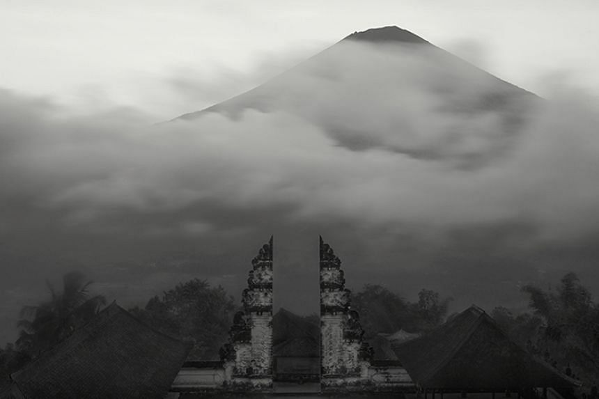 A black-and-white photograph featuring a view of Mount Agung in Bali.
