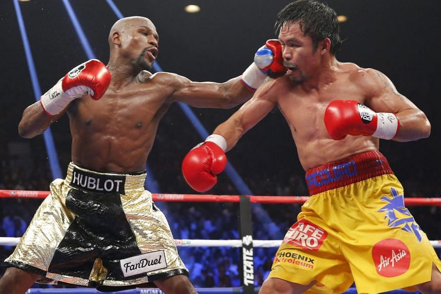 Floyd Mayweather, Jr. (left) lands a left to the face of Manny Pacquiao in the 11th round during their welterweight WBO, WBC and WBA title fight in Las Vegas, Nevada, on May 2, 2015.