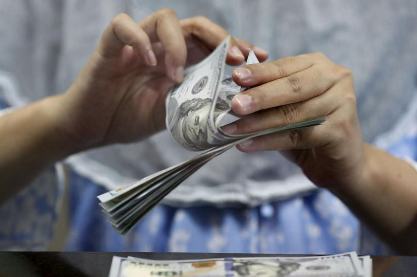 A teller counts U.S. dollars at a money changer in Jakarta, Indonesia on May 18, 2015.