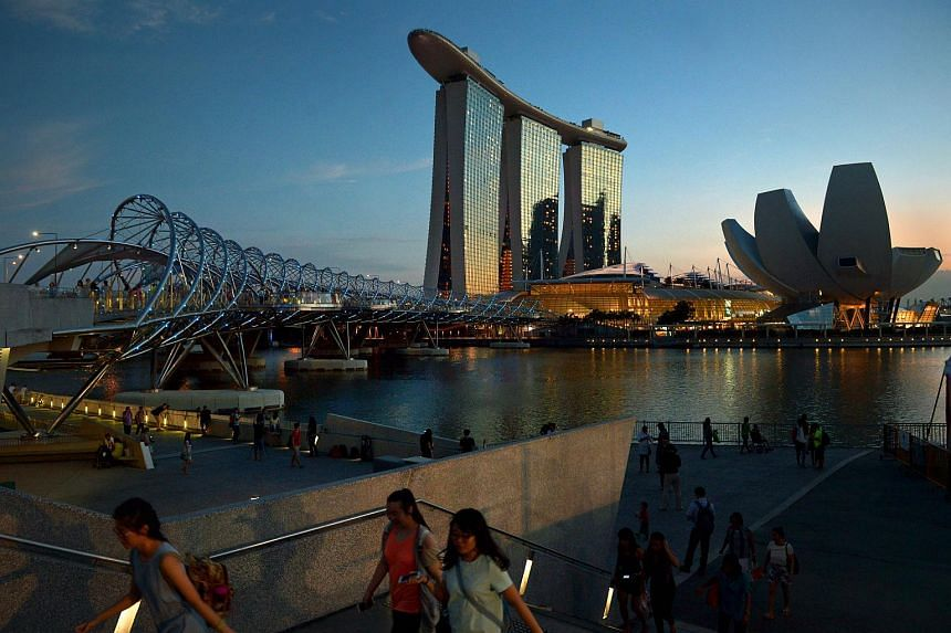 Tourists walking along the path to the Helix Bridge, with the Marina Bay Sands and ArtScience Museum in the background at dusk.
