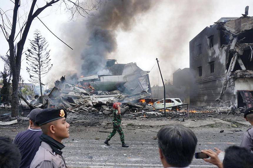 Indonesian police and military officials secure the crash site of a military Hercules plane in Medan, North Sumatra province on June 30, 2015.