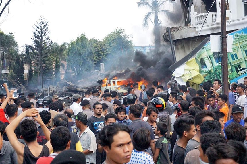 Residents gather next to the crash site of a military Hercules plane in Medan, North Sumatra province on June 30, 2015.