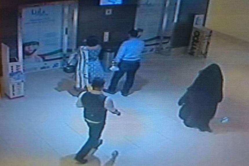A file CCTV image released by Abu Dhabi police on December 3, 2014 shows a fully veiled woman (right) walking in a shopping mall in the Emirati capital.