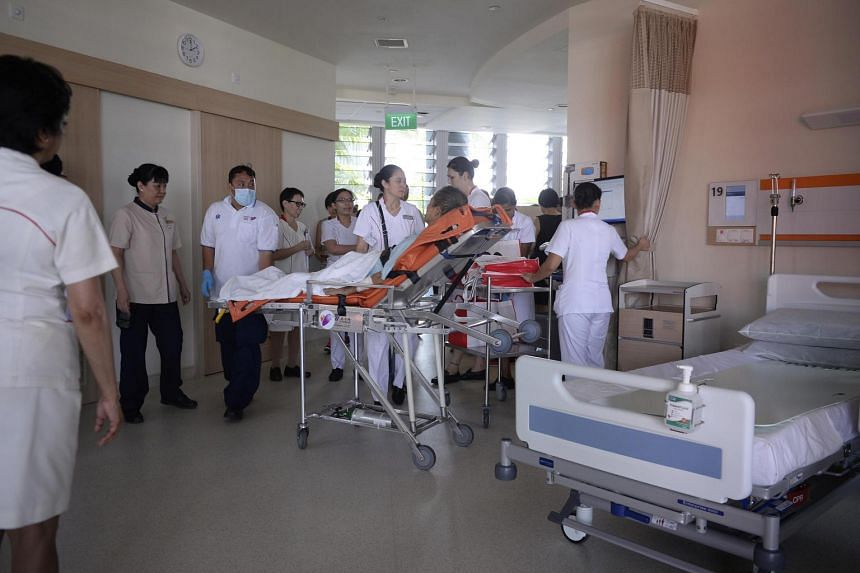 Hospital staff help an unidentified patient settle into Ng Teng Fong.