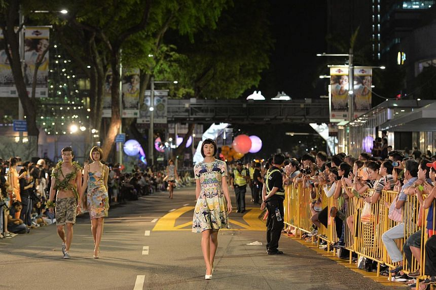 Models walking down Orchard Road on April 11, 2015.
