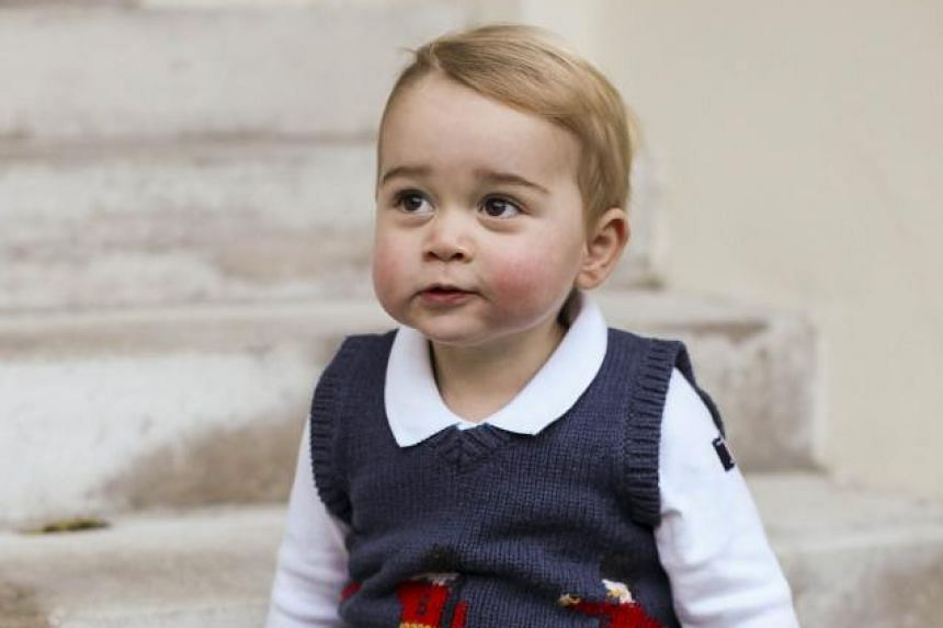 Britain's Prince George of Cambridge sitting in a courtyard at Kensington Palace in London.