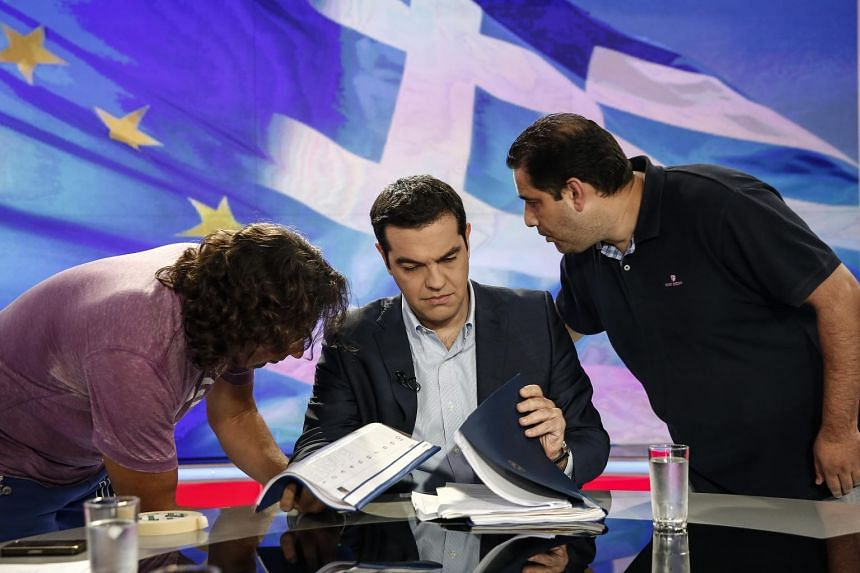 Alexis Tsipras, Greece's prime minister, centre, waits for a televised interview to start inside a studio of Greek state television broadcaster ERT in Athens on Monday.