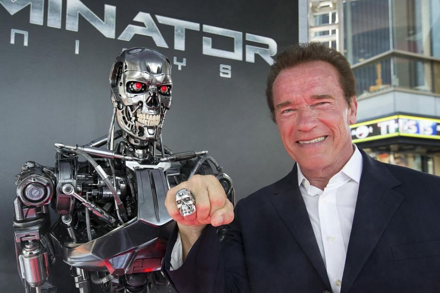 Cast member Arnold Schwarzenegger poses by a Terminator replica at the premiere of  Terminator Genisys in Hollywood, California on Sunday.