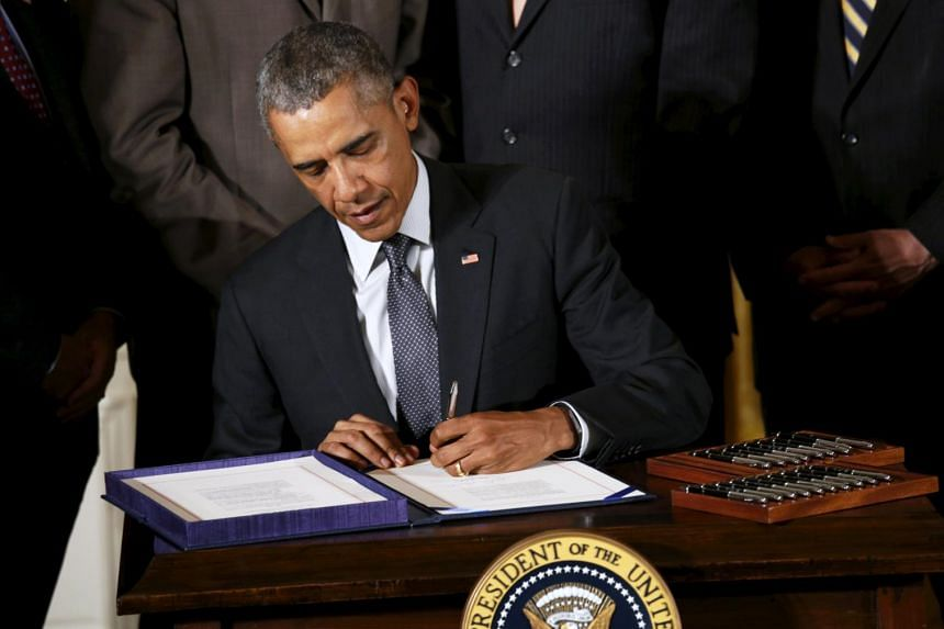 """US President Barack Obama takes part in a signing ceremony for the """"fast-track"""" trade bills on Monday."""