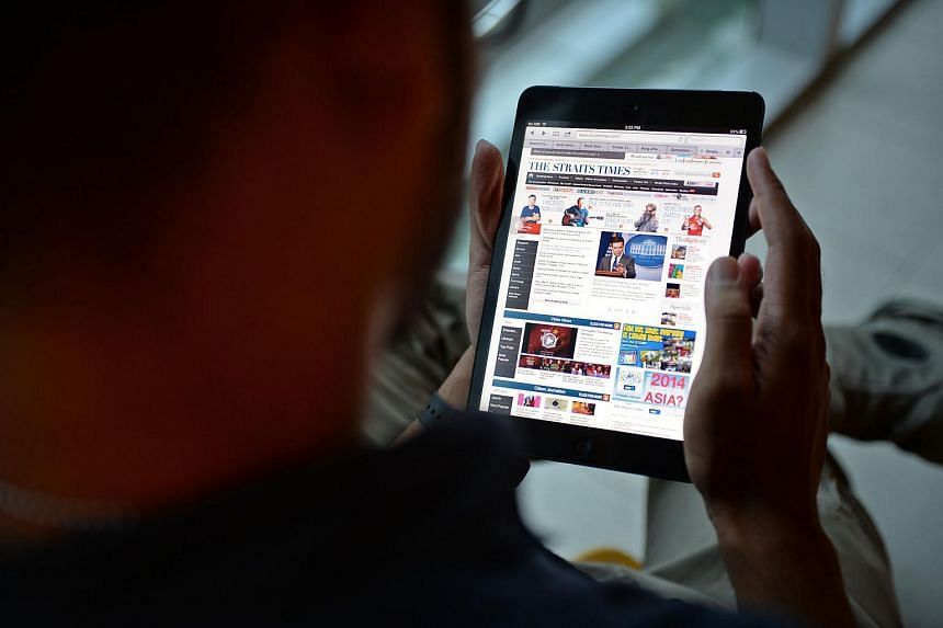 A man reading an online edition of The Straits Times.