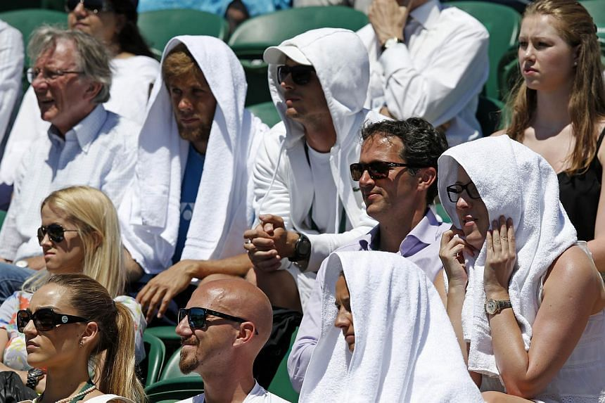 Spectators wear towels on their heads to shade them from the sun on day two of the 2015 Wimbledon Championships at The All England Tennis Club in Wimbledon, south-west London, on June 30, 2015.