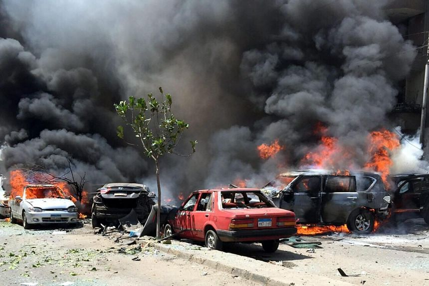 Smoke and flames rise above burning cars at the scene of a bombing targeting the convoy of the Egyptian prosecutor-general, in a northern suburb of Heliopolis, Cairo, Egypt on June 29, 2015. PHOTO: EPA