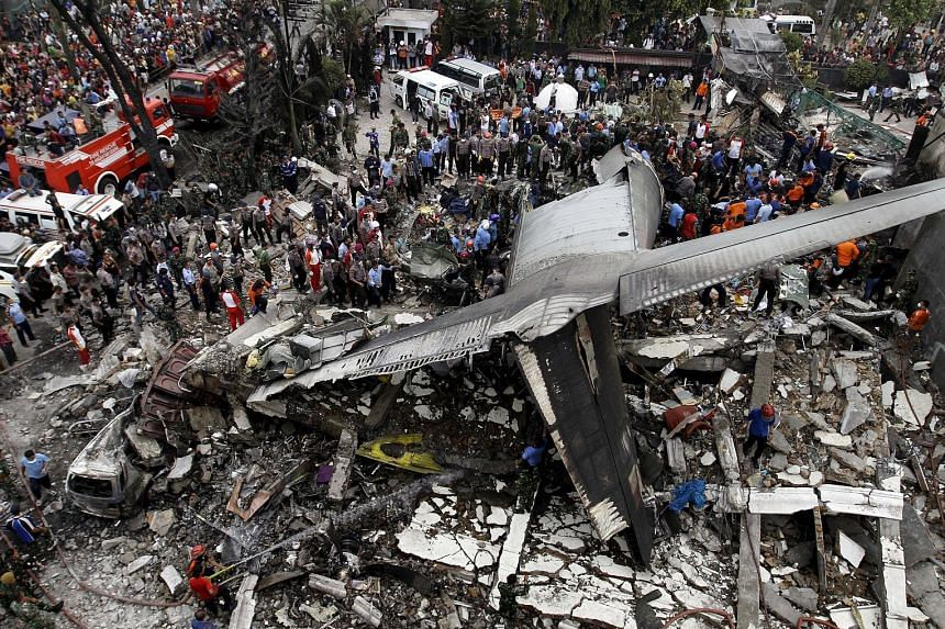 Security personnel and rescue teams examining the wreckage of an Indonesian military C-130B Hercules transport plane, which crashed into a residential area in Medan yesterday. An Air Force spokesman said it was unclear what caused the crash.