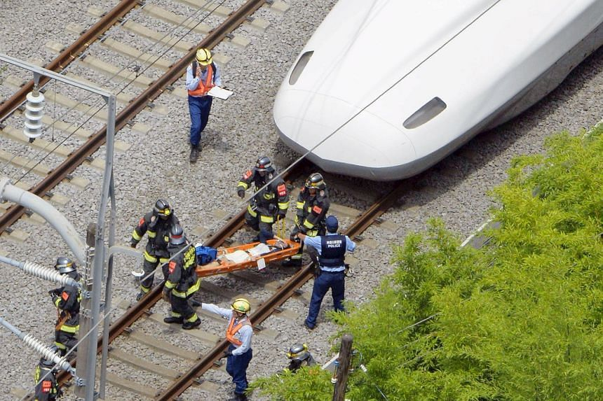 Rescue workers carrying a passenger from the Shinkansen bullet train after it made an emergency stop in Odawara, south of Tokyo.