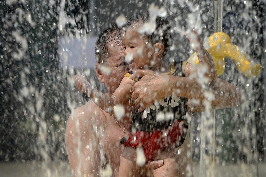 Mr Bobby Lim and his 11-month-old grandson Javen at the Sports Hub water park yesterday.