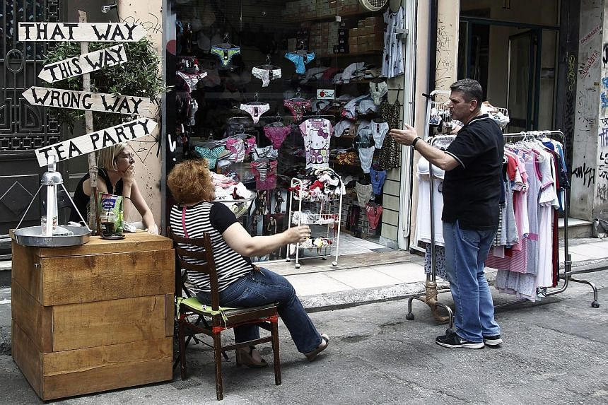 Shop owners in Athens. Greek jitters proved to be short-lived as the STI rebounded yesterday, says analyst Liu Jinshu.