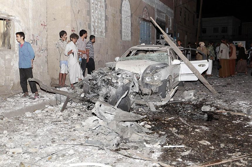 Debris strewn across the street in Sanaa after Monday's car bomb attack, which killed at least 28 people.