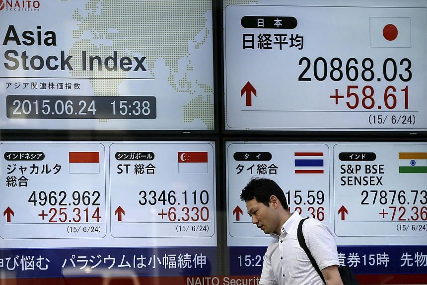 A man walking past an electronic board displaying various Asian countries' stock price index outside a brokerage in Tokyo.
