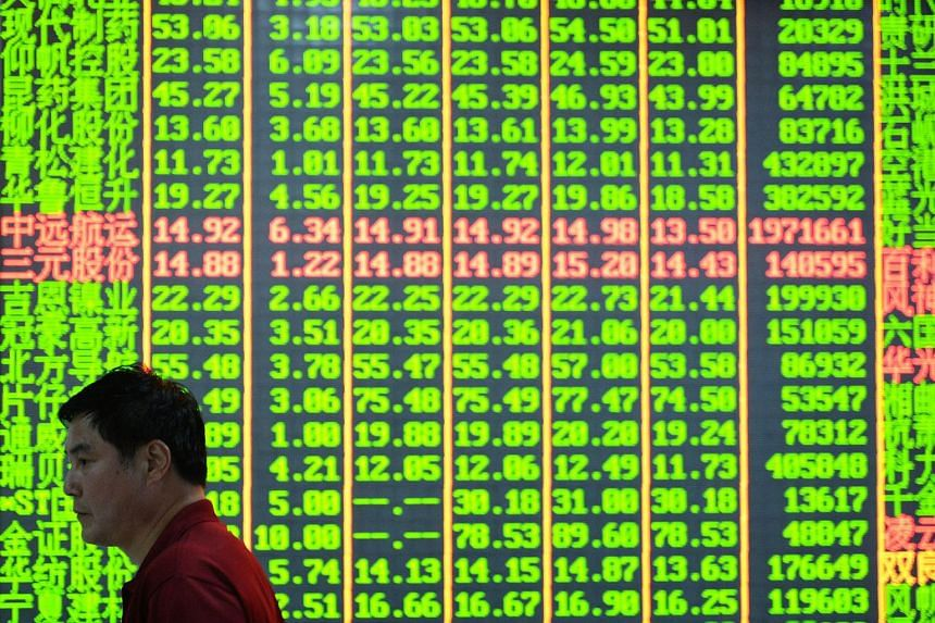 A man walking past a share prices board at a security firm in Hangzhou, eastern China's Zhejiang province.