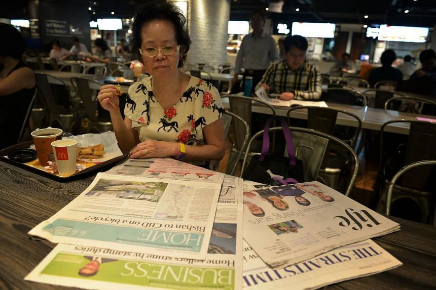 Insurance consultant Christina Han, 55, browsing through her ST copy at the food court in Clifford Centre.