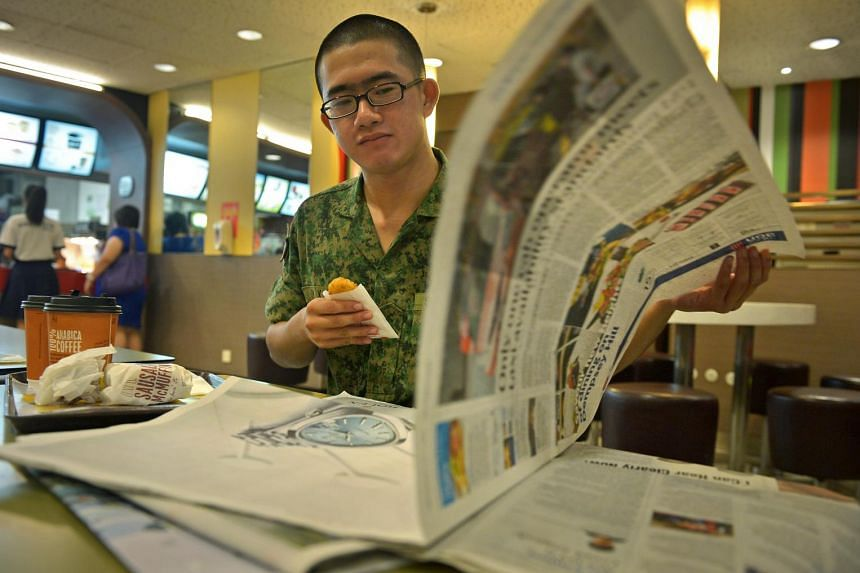 Full-time national serviceman Tow Ying Xiang, 19, reading a copy of ST.
