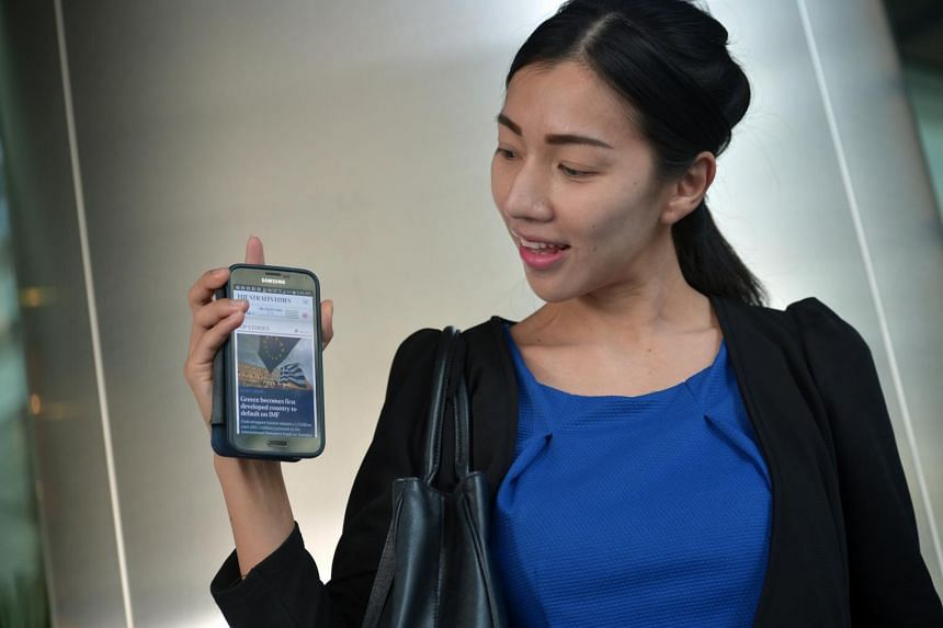 Telemarketer Manichanun Thanachaisethakul, 31, showing the revamped ST website on her mobile phone.