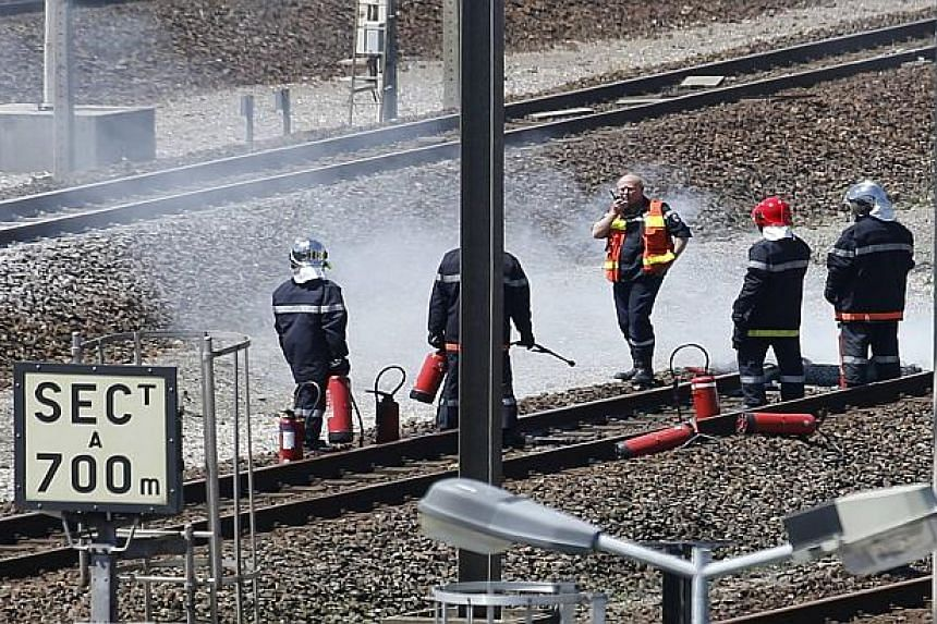 Firemen inspect the Eurotunnel tracks after workers set fire to tyres on them, disrupting services.