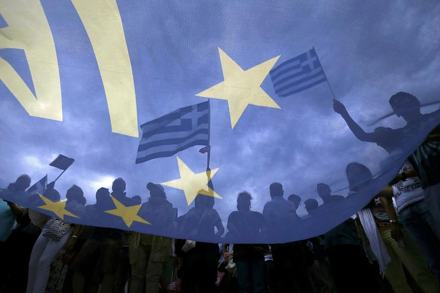 Pro-Euro protesters holding Greek flags in Athens.