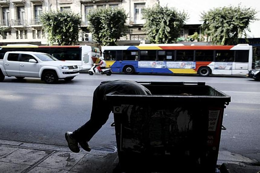 A man searches the contents of a bin in Thessaloniki, Greece, on June 30, 2015.